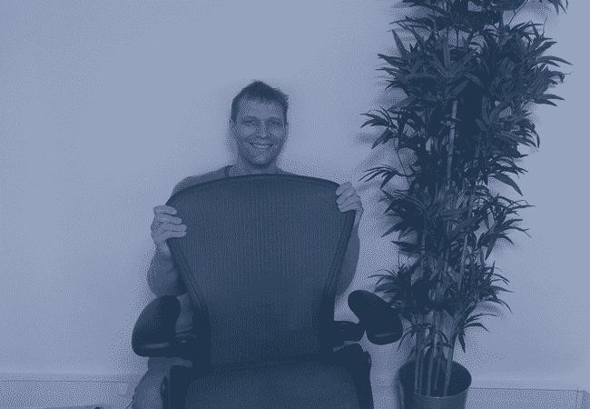 Christophe Cote qui se cache derrière un fauteuil de bureau
