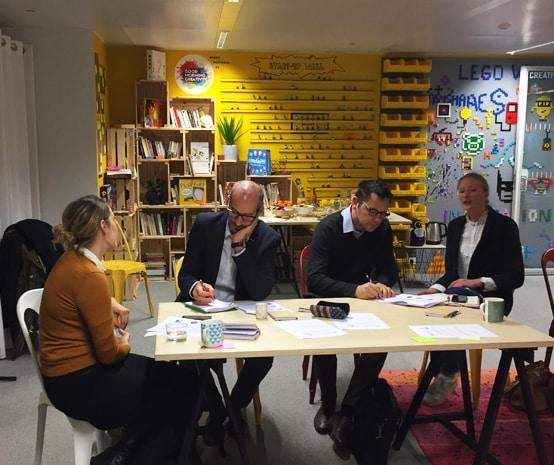 Photo de 4 personnes discutant autour d'une table à Station F